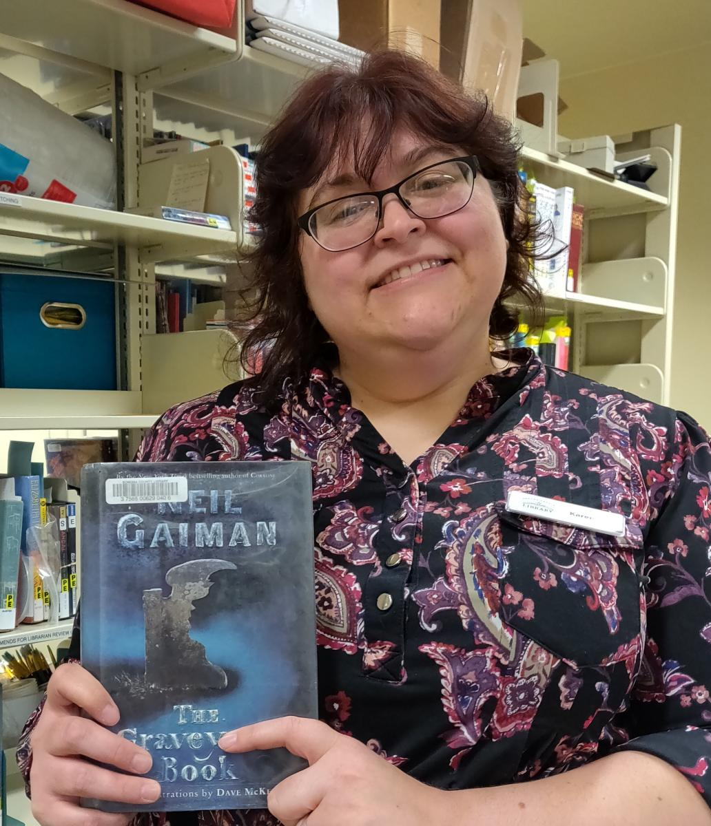 "woman holding book ""The Graveyard Book"" by Neil Gaiman"