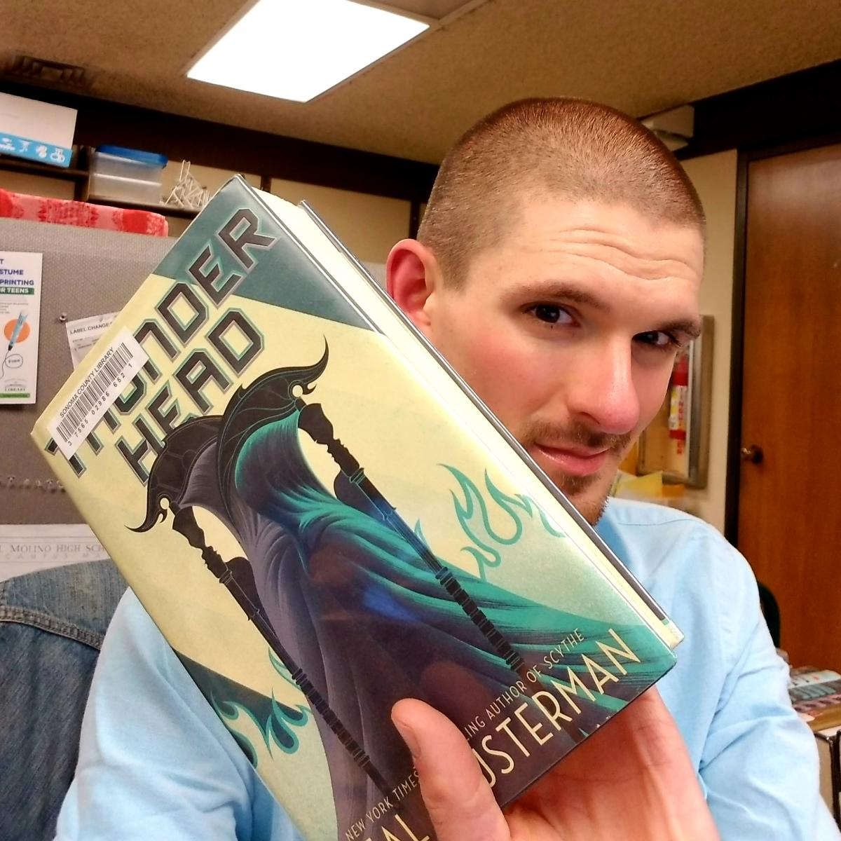 "man holding book ""Thunderhead"" by Neal Shusterman"