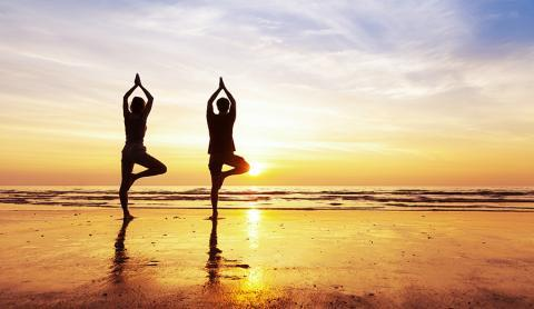 Young man and woman doing yoga on beach at sunset.