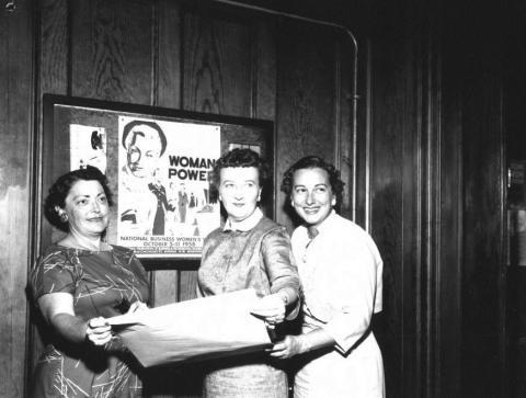 Three Petaluma Women Stand in Front of a National Business Women's Week Poster - 1958 photo