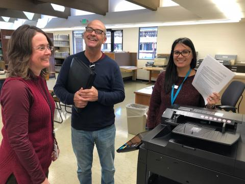 Staff assist patron with new photocopier.