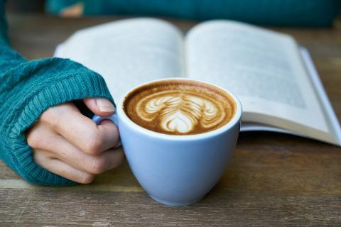 Teen with book and coffee.